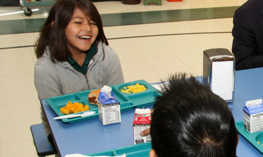 A young smiling Native American girl with long dark hair smiles and sits at a lunch table talking to a boy.
