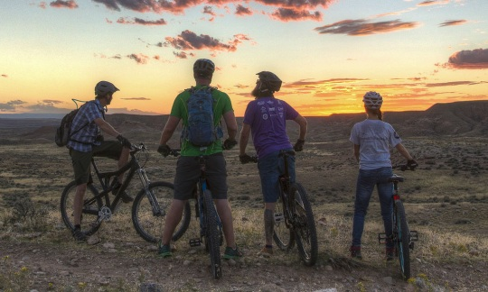 Four people rest on mountain bikes on a ridge overlooking a desert plain at sunset.