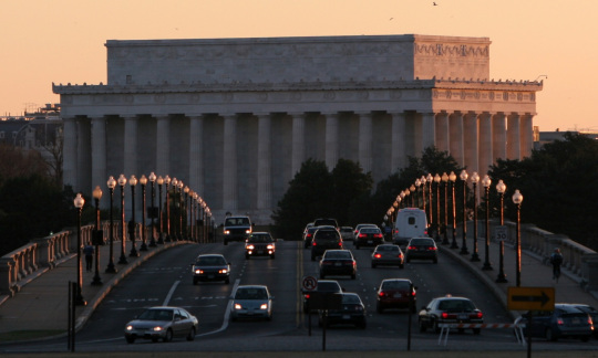 Cars drive over a concrete bridge with the flat topped Lincoln Memorial in the background.