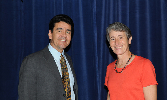 Deputy Secretary Mike Connor and Secretary Sally Jewell standing in front of a blue curtain.