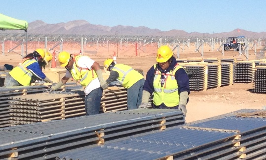 Workers wearing safety equipment move pallets of materials at a construction site in the Nevada desert.