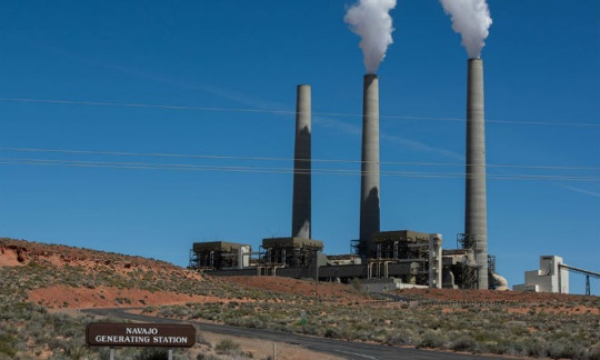 Large power plant with tall smoke stacks established on prairie against a blue sky