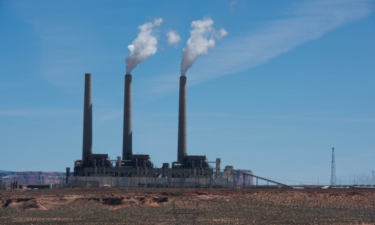 Three smoke stacks rise above a large power station sitting on a desert plain.