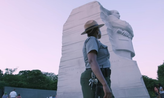 A female park ranger walks through a memorial looking up at a large stone statue of Dr. Martin Luther King Jr.