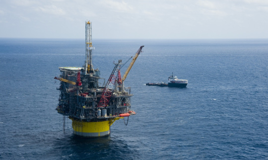 An offshore oil rig stands above the water with a ship floating nearby on the Gulf of Mexico.