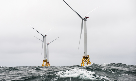 Three large metal towers with propeller turbines float on the surface of the ocean.