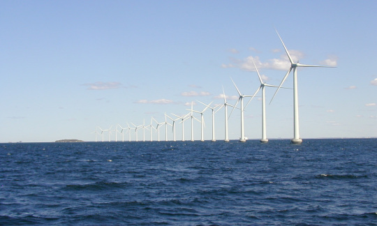 A line of twenty large wind turbines curves across the ocean on a clear day.