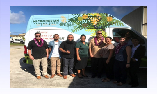 Assistant Secretary Domenech and OIA Director Pula (with leis) visit with Micronesian Resource Center Team on Guam  pictured in front of M.A.I. Van in April 2018 (photo DOI/HBlanco)