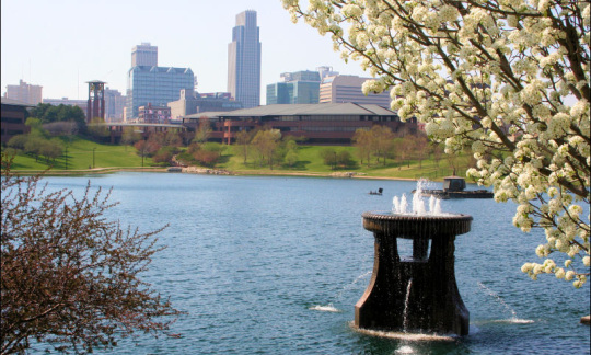 A view of a pond in a park with the Omaha, Nebraska skyline in the background.