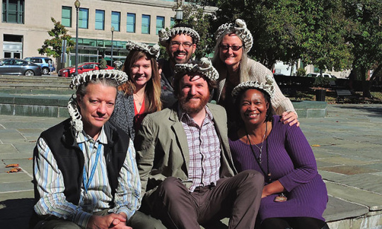 A group of men and women with fake snakes crowning their heads.