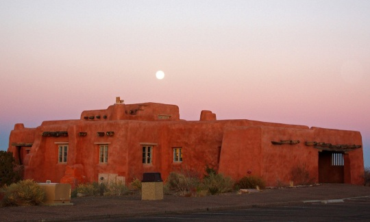 A large red adobe building stands on a desert plain under a sunset sky with a rising full moon.