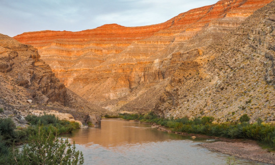 A calm, brown river flows between the steep brown walls of a low canyon.