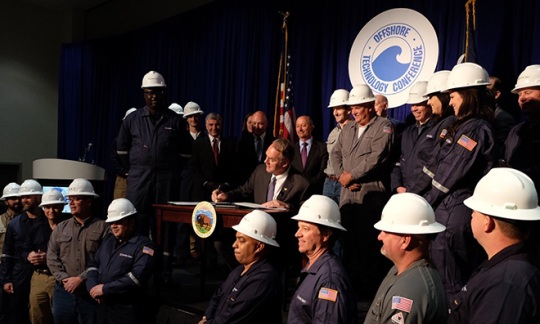 Secretary Zinke signs a secretarial order, surrounded by people in white hard-hats.
