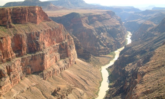 A river snakes through the valley, with bright orange cliffs on either side looming up.