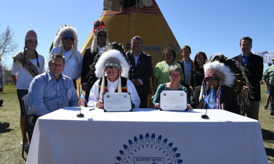 Senator Jon Tester, Blackfeet Chairman Harry Barnes, Secretary Jewell and Chief Earl Old Person sitting at a table holding the signed document.