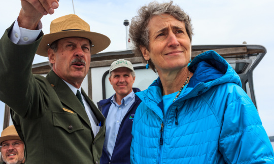 Secretary Jewell and a park ranger in uniform stand on a boat and look off into the distance.