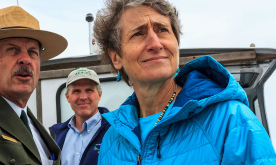 Secretary Jewell standing on a boat looking into the distance.