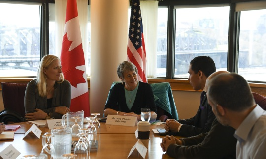 Secretary Jewell and Canadian officials sitting around a table in a conference room with national flags behind them.
