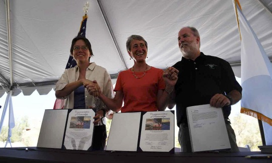 Secretary Jewell stands between two other officials displaying a signed agreement in binders.