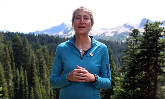 Secretary Sally Jewell standing in front of a forest with a snow capped mountain in the background.