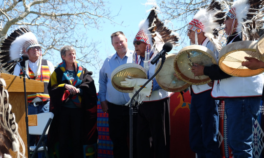 Secretary Jewell stands on a stage with a group of Native Americans who are singing.