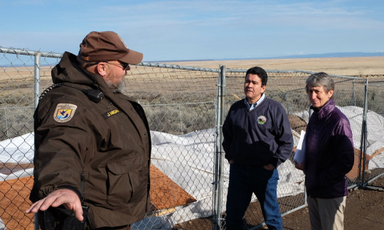 Secretary Jewell and Deputy Secretary Connor talking to a U.S. Fish and Wildlife employee while standing near a fence and damaged area on a wildlife refuge.
