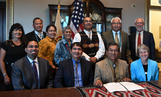 Secretary Jewell and ten tribal leaders pose around a table in an office.