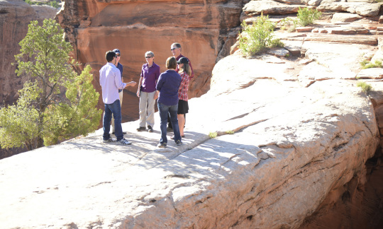 Secretary Jewell talks with a small group of people while standing outside in the rocky Utah landscape.