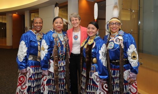 Secretary Jewell poses with four Native American women in colorful, traditional clothes.