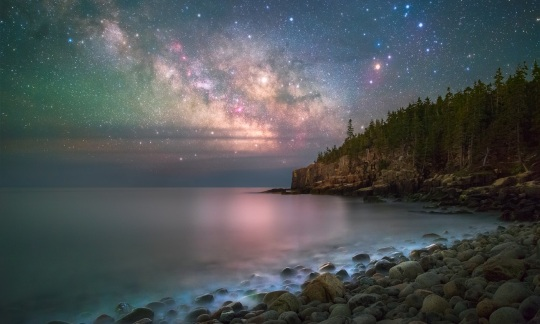 Clusters of bright stars glow in the night sky above the ocean and a rugged shoreline covered in rocks and trees.