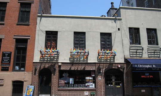 A photo of the Stonewall in, a brick building decorated with rainbow flags on a quiet street in New York City.