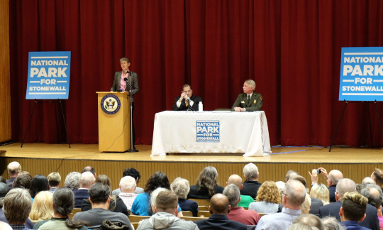 Secretary Jewell speaks at a podium, addressing a crowd of people in a meeting hall.