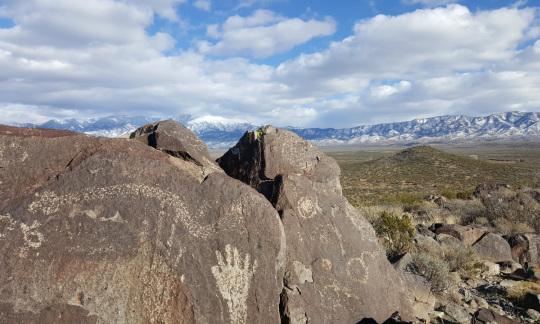 Native American rock art on stones in a desert landscape.