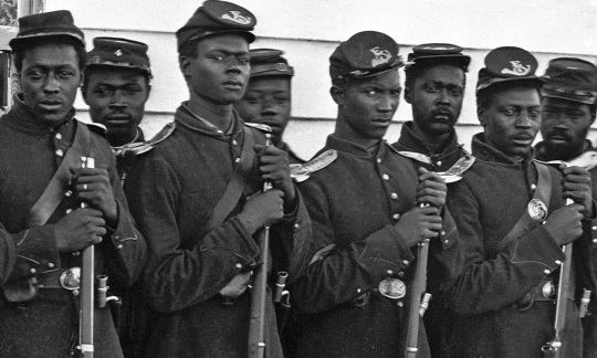 Historic black and white photo of two lines of african american soldiers wearing civil war uniforms.