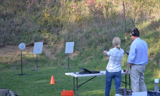 A blond white woman stands behind a table and points a handgun at a target in the grassy field in front of her as a tall white man stands nearby watching.