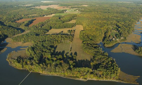 An aerial view of Werowocomoco with trees, fields and water.