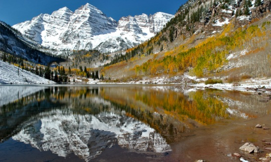 A still lake reflects the autumn trees and snow capped mountains surrounding it.