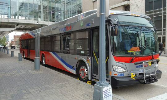 A large city bus is parked at the curb of a street.
