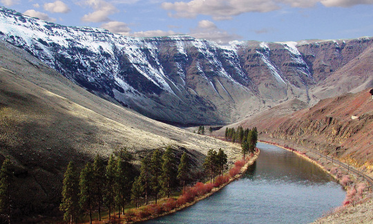 A river winds through a valley with snow-capped mountains in the background.