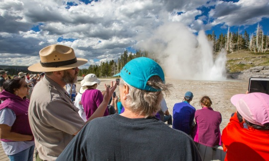 A park ranger talks to park visitors as a geyser goes off in the background.