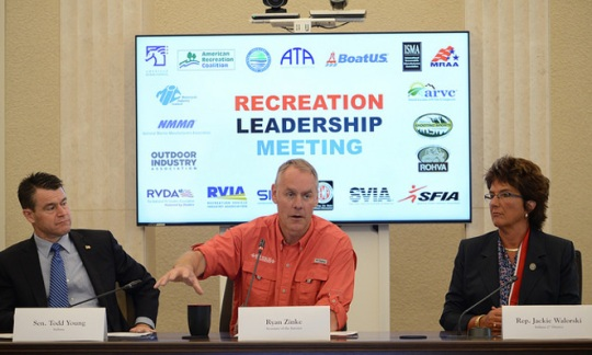 "Secretary Zinke sits between a man and a woman under a sign saying ""Recreation Leadership Meeting"" with many logos"