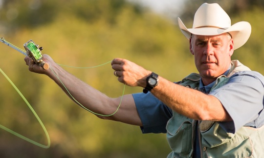Ryan Zinke wearing a cowboy hat and fly fishing in a river.