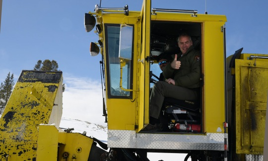 Secretary Zinke in a large yellow snow plow on a clear day