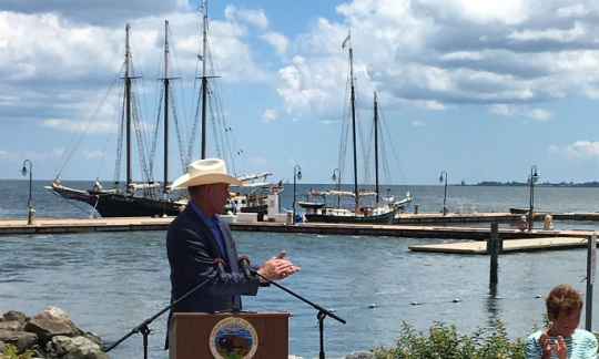 Secretary Zinke stands at a lectern speaking wearing a hat with a blue sky and wooden sailing ships in a harbor