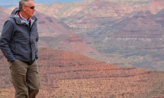 Secretary Zinke stands on a ledge with dusty, rocky hills in the background in the desert