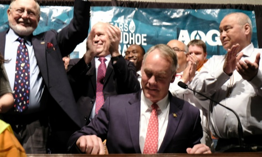 Secretary Zinke wears a suit and sits at a table signing a piece of paper as a group of people stand around him cheering.