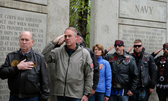 Secretary Zinke stands with a small group of people next to an outdoor veterans memorial.