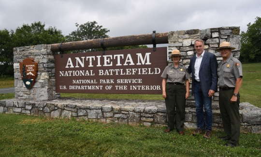 Secretary Zinke stands with two park rangers next to a wooden sign for Antietam National Battlefield.