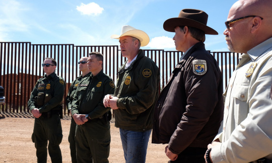 Secretary Zinke wears a cowboy hat and stands in a line with border patrol officers in front of a tall metal wall.
