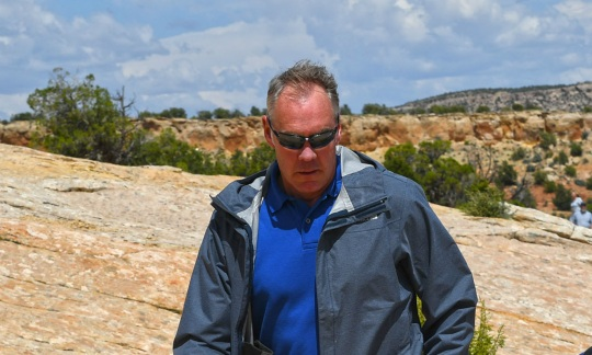 Secretary Zinke wears a light gray jacket and sunglasses and walks along a rocky trail with a small group of people.